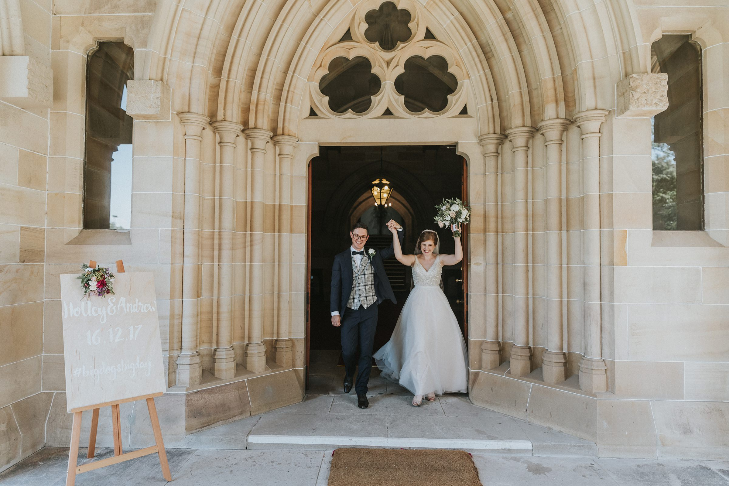 bride and groom celebrate at the door to the chapel at the university of sydney