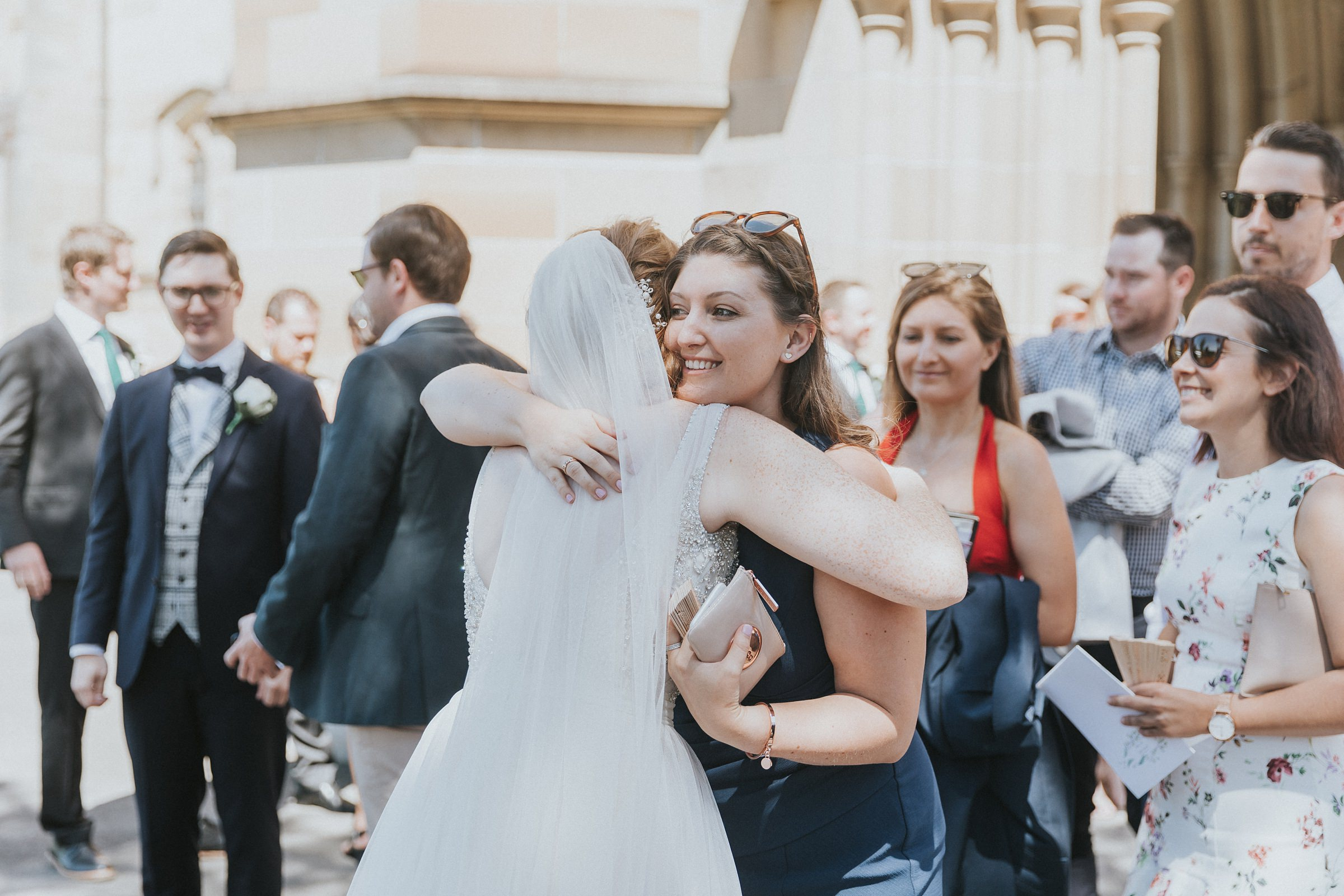 hugs for the bride and groom after catholic wedding ceremony